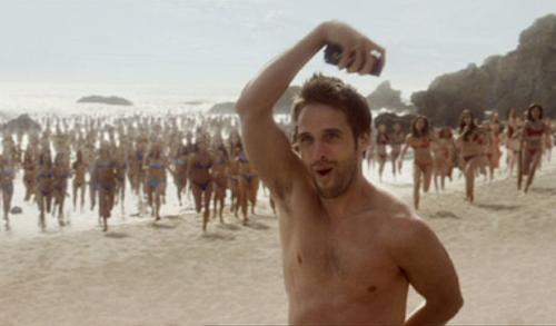 Lynx effect tv advert still. man on beach with women running towards him